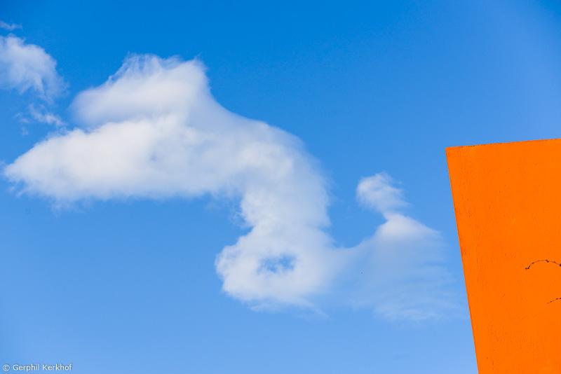 een wolk die lijkt te ontsnappen aan een oranje gebouiw verzinebeeldt de kracht van unfocus